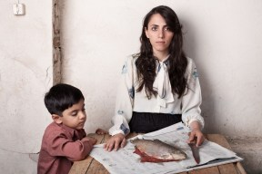Woman with child cutting fish that lies on a table