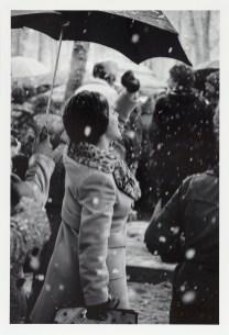 a woman under umbrella during snow