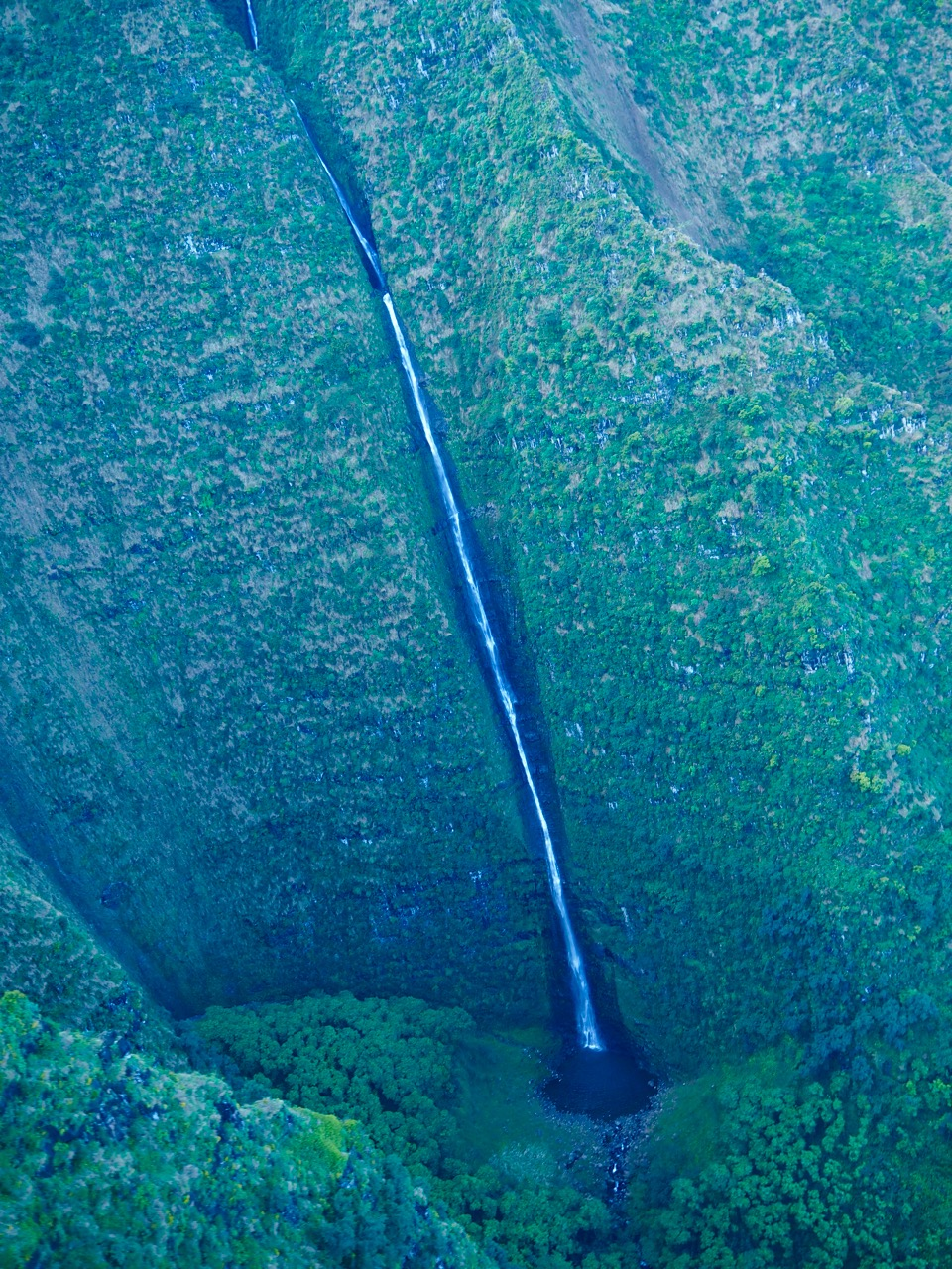 A very tall waterfall flowing off the Na Pali Coast.