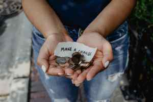 person holding change and money in hands, learn lifestyle tips to save money