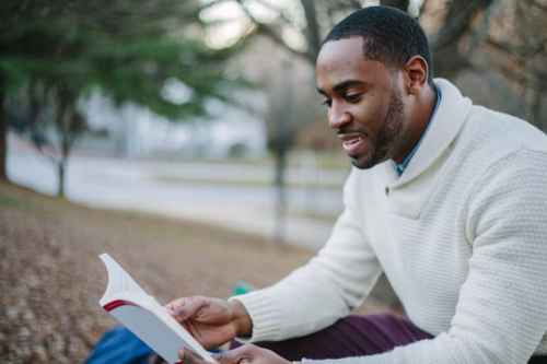 man smiling reading book