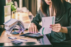 asian-woman-with-financial-bills-calculating-debt