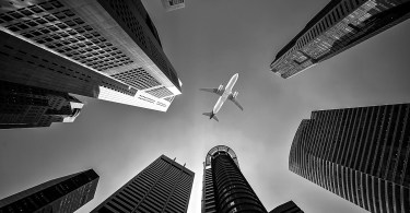 Black and white image looking between skyscrapers at an airplane overhead.