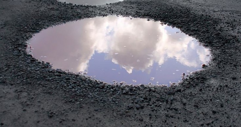 Pothole filled with water, reflecting a blue sky.