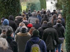 Trauernde auf dem Weg zur Urnen-Bestattung