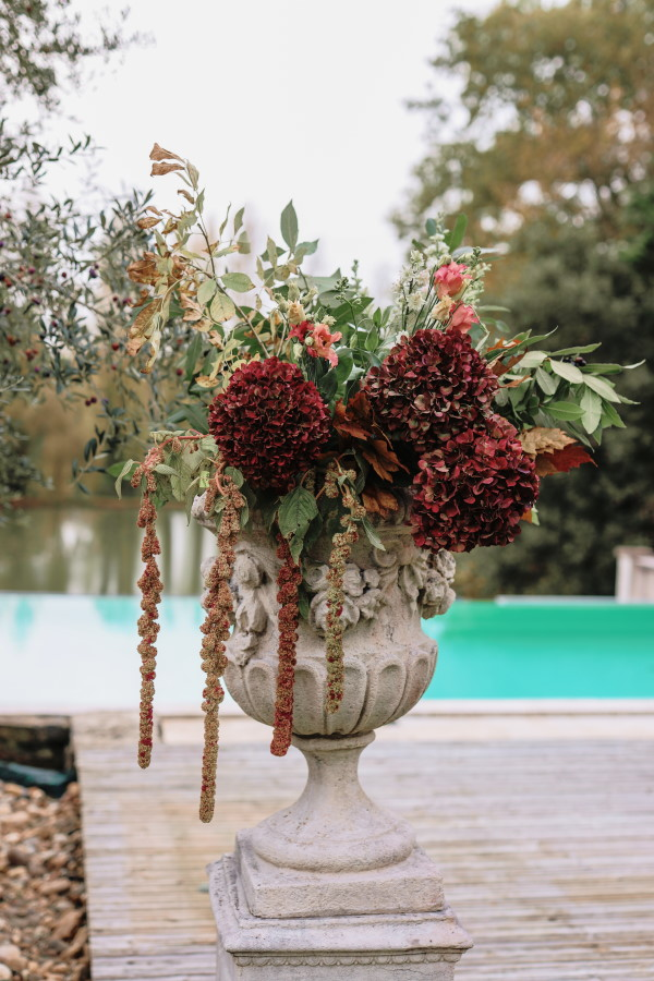 Arrangement floral bourgogne, rose et eucalyptus dans un vase en pierre Médicis