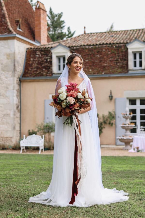 La mariée se tient à l'extérieur du Château Lacanaud tenant un bouquet de bourgogne et blanc et sourit vers son marié
