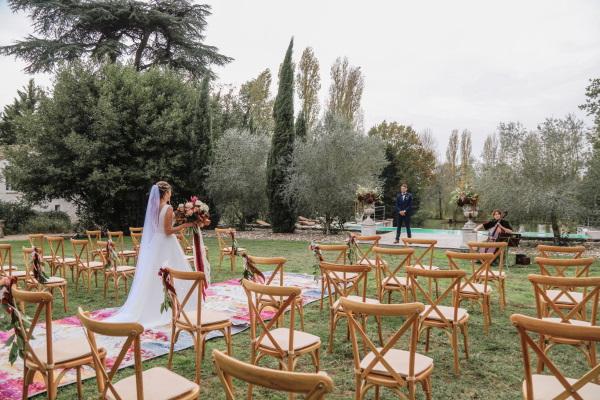 La mariée marche dans l'allée moquettée extérieure sur l'herbe vers son marié