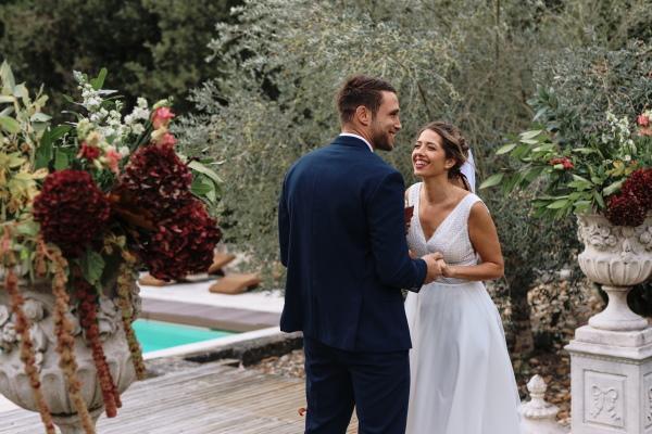 la mariée et le marié se sourient après que leurs vœux soient terminés, entourés d'arrangements floraux bordeaux