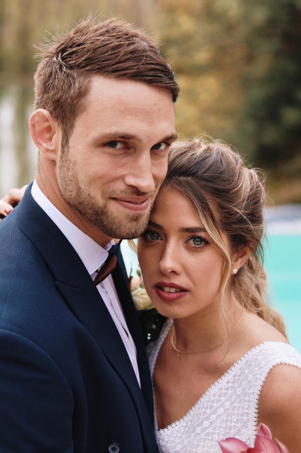 les mariés sourient près de la caméra - il porte un costume bleu marine et elle a une robe blanche et élégante
