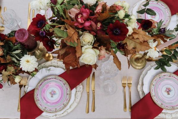 Le bouquet de mariées est posé sur la table de mariage avec des fleurs bordeaux et des décorations de table et des couverts dorés
