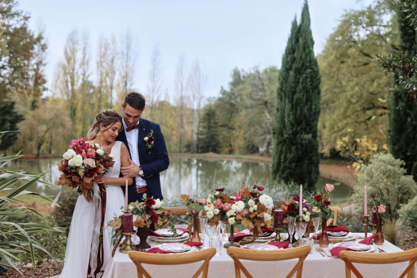 Les mariés se tiennent à la table de mariage en face du lac extérieur et de grands arbres verts