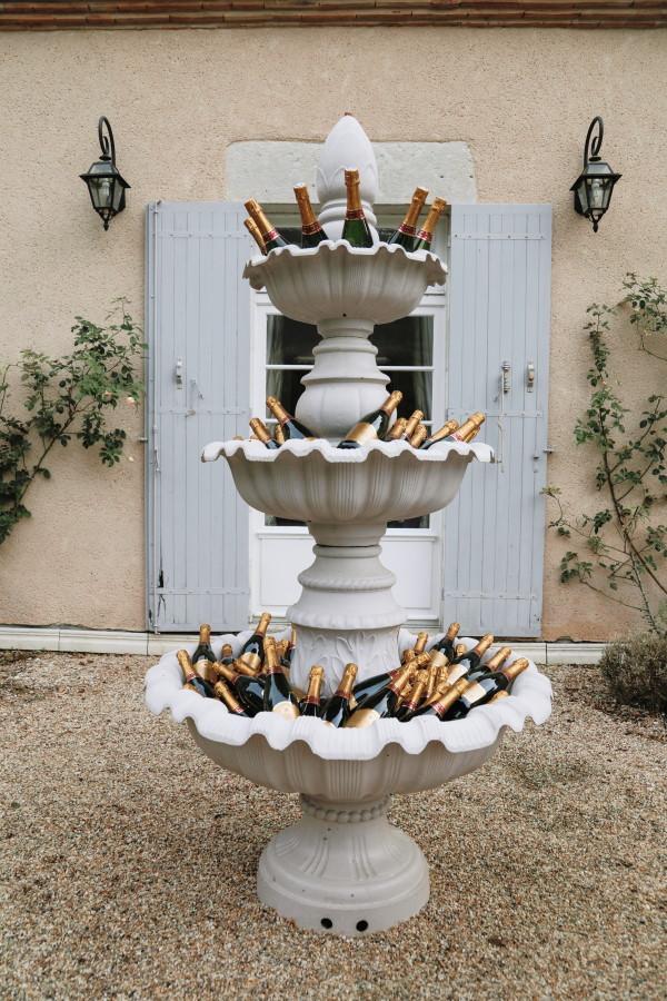 des bouteilles de champagne remplissent une fontaine d'eau extérieure en pierre à 3 niveaux pour les invités du mariage