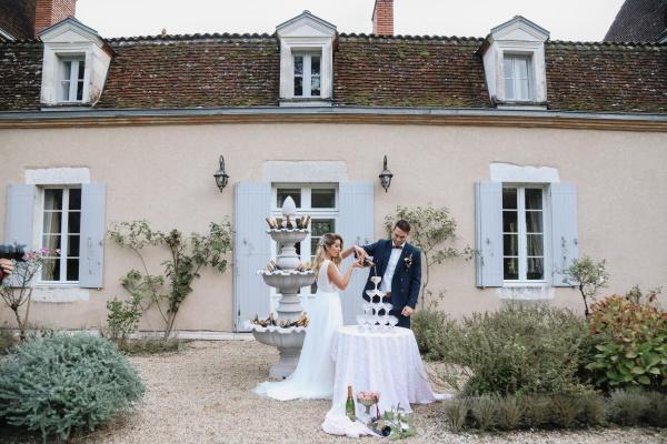 Les mariés commencent à verser du champagne dans la tour à champagne du château lacanaud