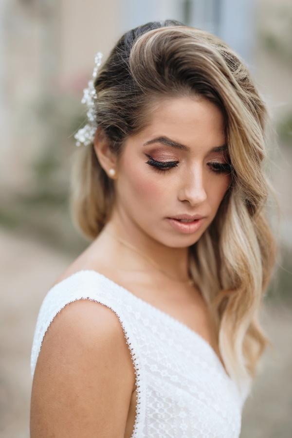 Mariée avec côté balayé les cheveux blonds et accessoire de cheveux perle blanche épinglée dans