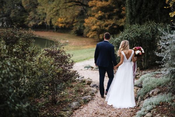 Les mariés descendent les marches du jardin du château Lacanaud en France avec dos à la caméra