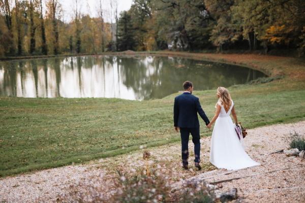 Les mariés se tiennent la main alors qu'ils traversent l'herbe vers le lac au château Lacanaud en Dordogne, France