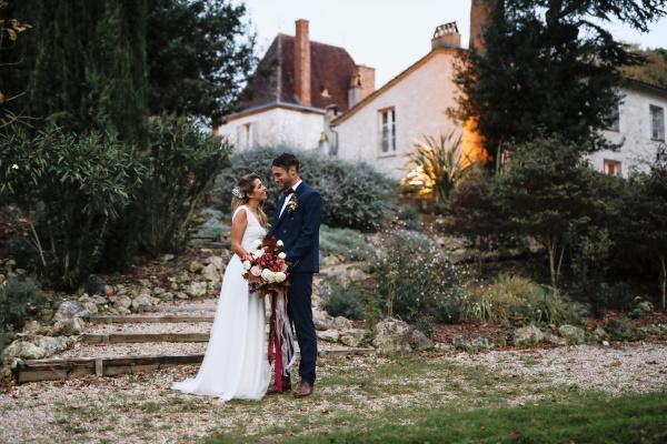 Couple marié se tient au pied des marches à l'extérieur de Château Lacanaud en Dordogne France