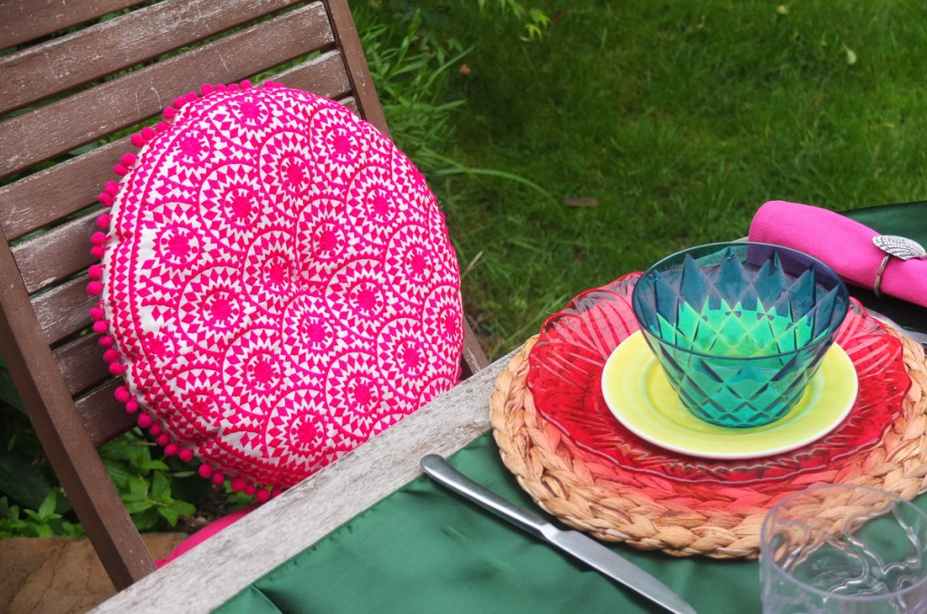 Gorgeous bright pink boho style round cushion with pompom trim from Sweetpea and Willow