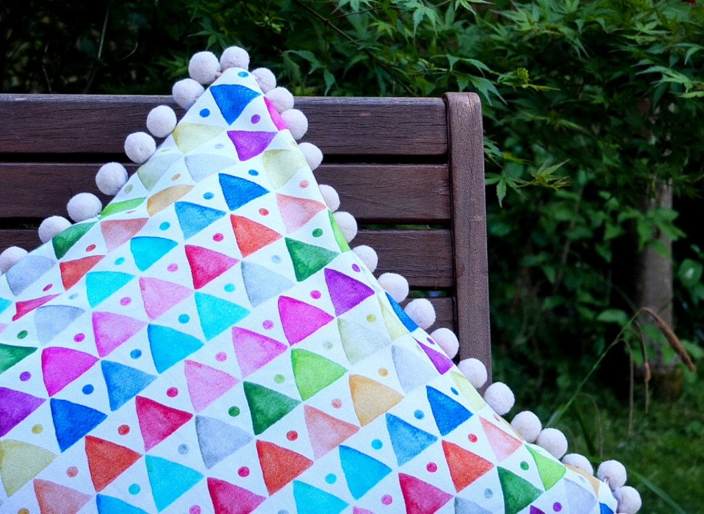 Love this colourful and contemporary geometric triangle design cushion - the pompoms finish it off perfectly!