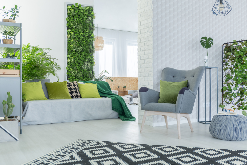 Use plants to create a vertical living wall in your home. As a bonus, it can help divide and create zones in your interior