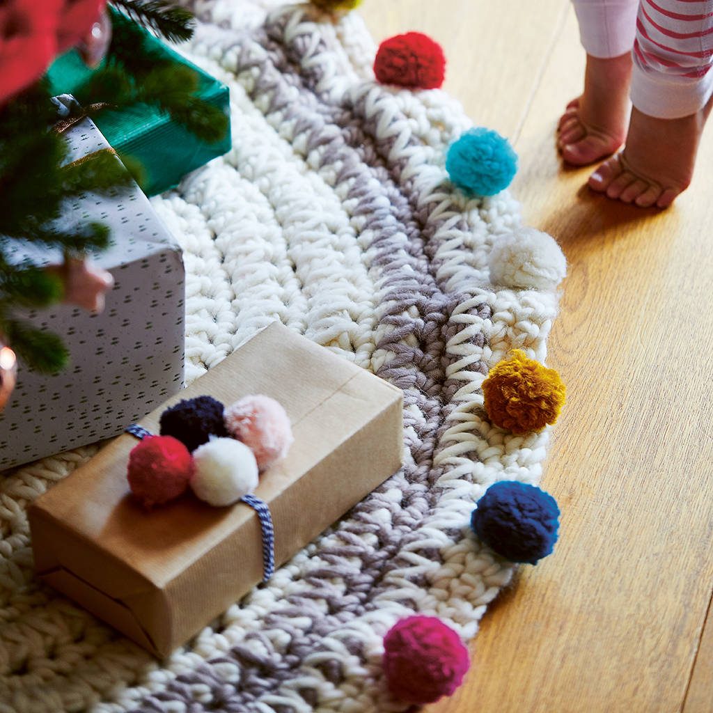 Chunky handmade crochet tree skirt with pom poms, perfect for a boho Christmas