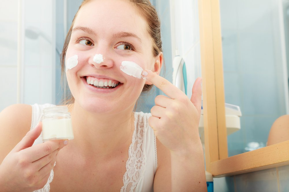 Woman applying moisturising skincare cream