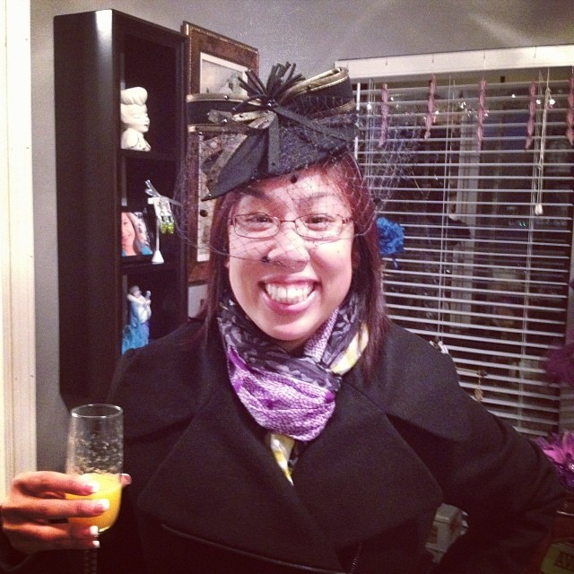 Sipping a mimosa while trying on a fascinator at Ava Marie's open house last year.