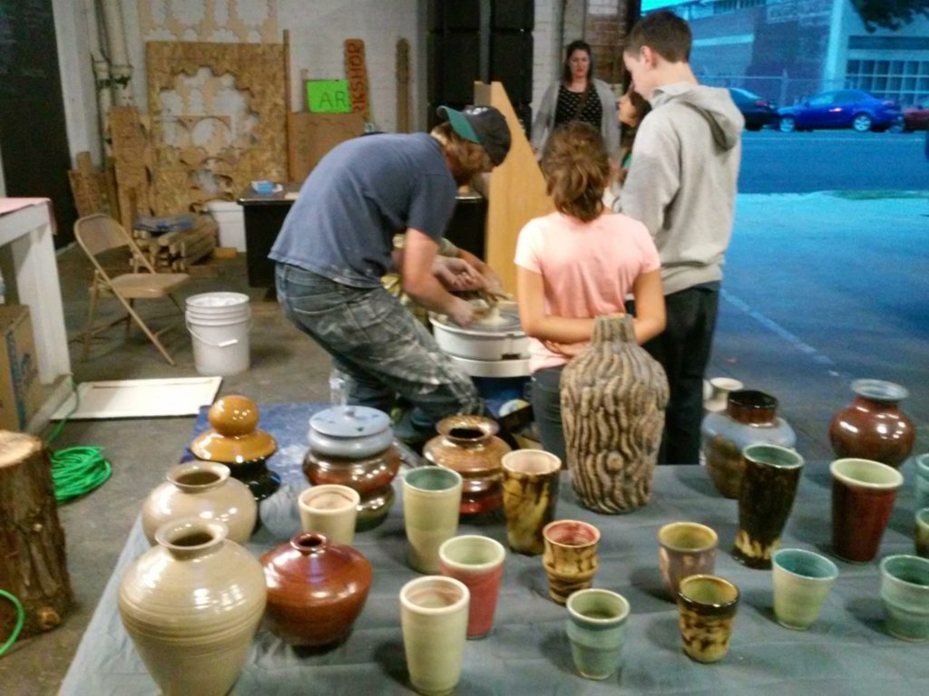 Showing some children how to use a pottery wheel during ArtHop.