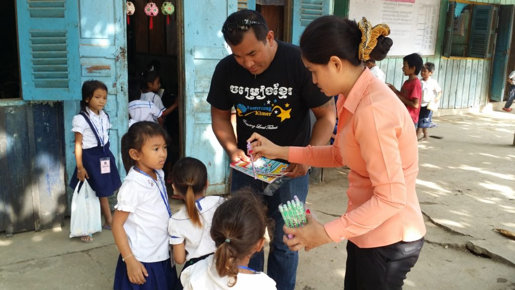 Kim handing out school supplies on his first trip to Cambodia