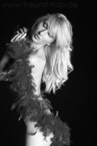 Blonde Frau posiert nackt in Federboa