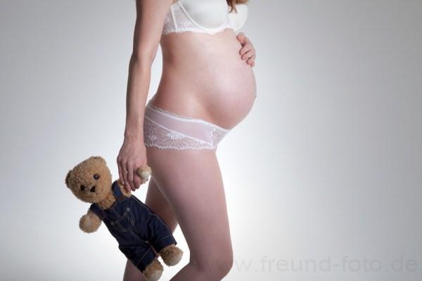 Schwangere Frau hält Teddybären