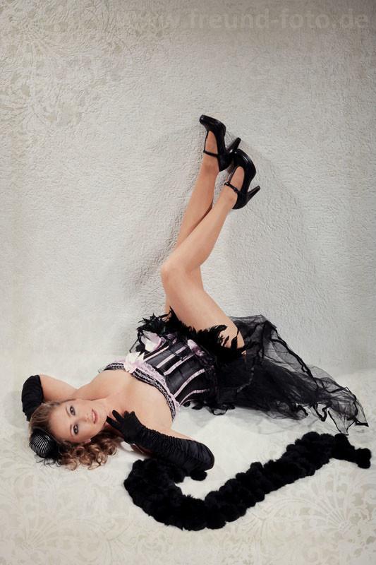 Frau im sexy Burlesque Outfit liegt an Wand