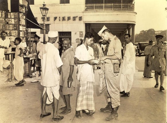 The GI tourist here ponders the purchase of a 'rare gem'---a typical camera study of life on Chowringheeduring the war. Firpo's famous restaurant is in the background, and dhoti-clad Indians and a British officer in shorts lend a bit of atmosphere.