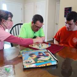 Team Member and Individuals playing board game.