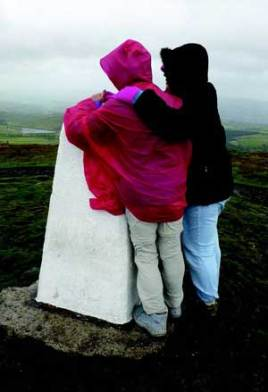 The author (in red) wiand Janet Ferguson hang on to keep from being blown away at the top of Pendle Hill. Courtesy the author.