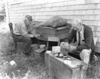 Dave Ryder, left, and Ben Gilley shuck scallops behind Dave's cottage at South Wharf, 1950. All four archival prints courtesy of the New Bedford Whaling Museum.
