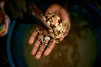 A boy sorts through rocks at a mine in Mongbwalu, Congo.