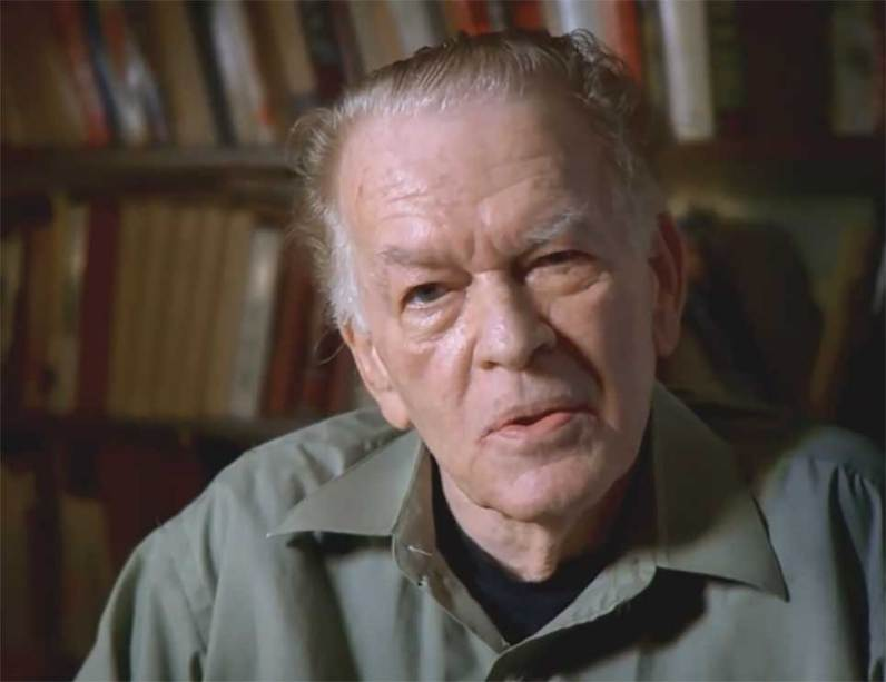 Gene Sharp, with some of his writings available through AEI. Picture courtesy an AEI video.