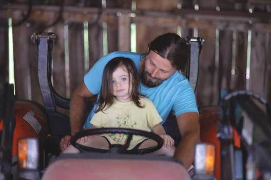 The author with child driving a tractor.