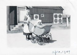 The author's great-grandmother Bernthal pushes her in a buggy; barn in the background.