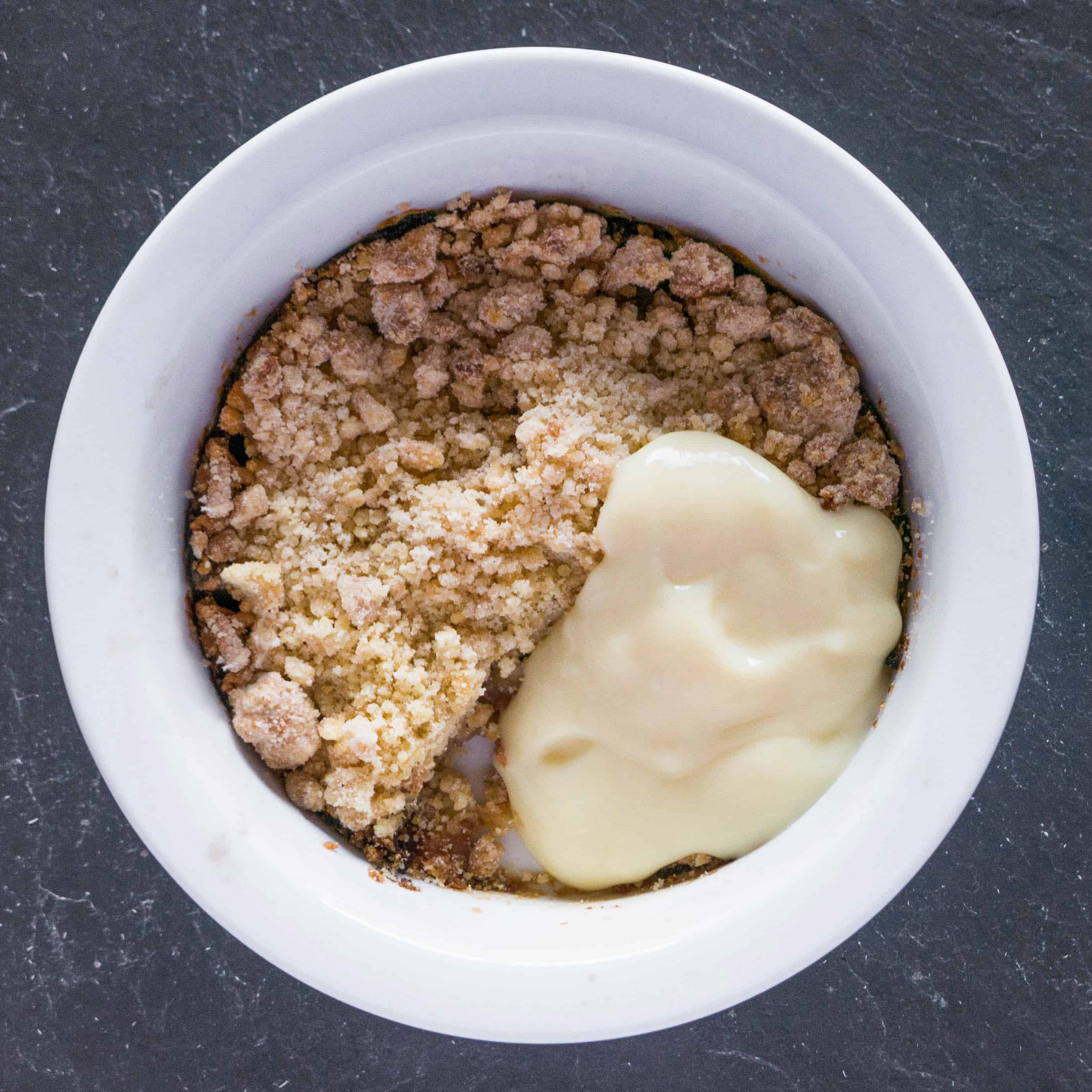 Gluten free, vegan, Bramley apple and quince crumble with vegan custard. Ready to eat.