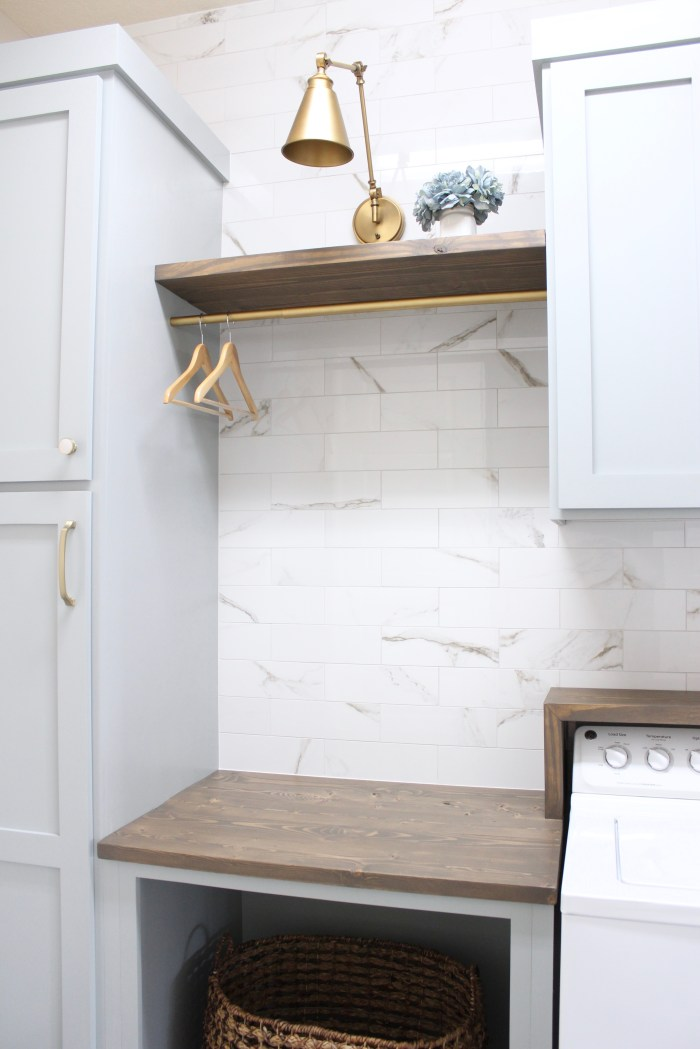laundry room-diy-blue-cabinets-easy-marble-wall-tile-gold-sconce-light-rustic-shelves-countertop