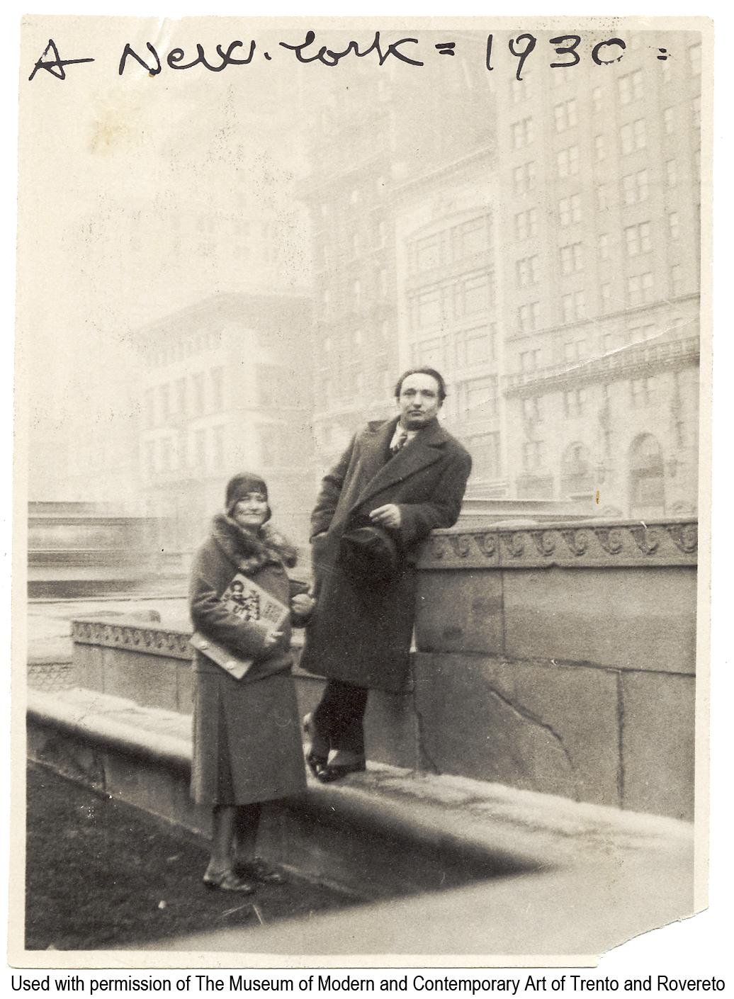 Dep.6.3.8 - «A New York - 1930». - New York, 1930. - 1 fotografia : b.n. ; 110 x 85 mm Pubblicato in: R. Antolini (a cura di), «Libri taglienti esplosivi e luminosi», 2005, p.134. Precedente segnatura Vol.850,|p.6 Sommario: Depero e Rosetta, con il libro imbullonato in mano, a New York sul tetto dell'Advertising Club in Park Avenue