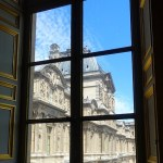 A view of the Louvre framed in a window.