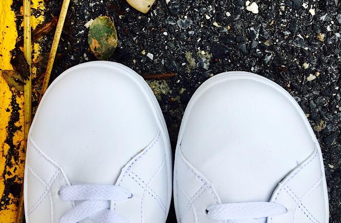 A pair of white sneakers on black asphalt.