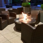 Wicker chairs surround a fire pit in front of the lobby.