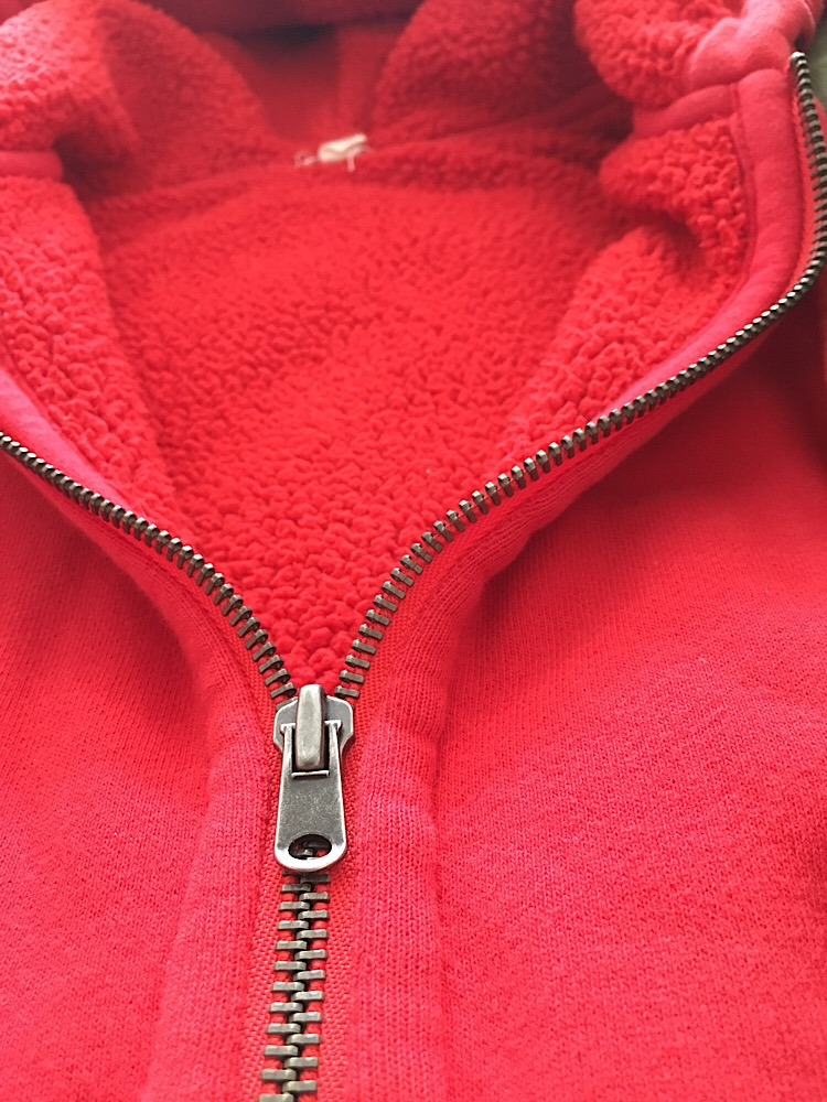 Close up photo of an open zipper of a red sherpa lined hoodie.