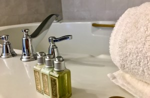 Photo of bathtub fixtures with a towel and L'Occitane products.