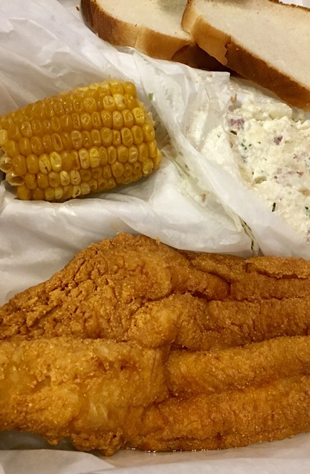 Fried catfish platter with corn on the cob, potato salad, and bread.